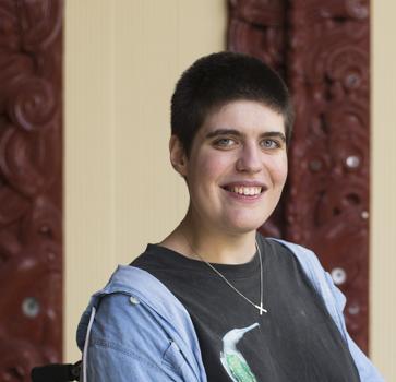 Woman in wheelchair smiles outside marae