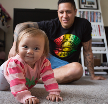 Baby smiling and crawling with father sitting behind