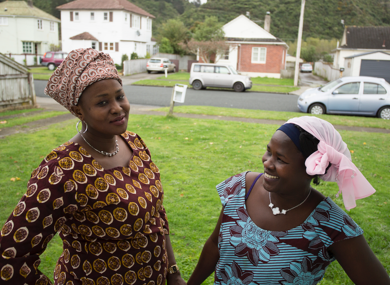 Two woman with head scarves stand on front lawn smiling