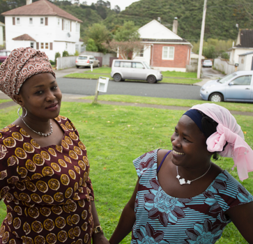 Two women with head scarves stand on front lawn smiling