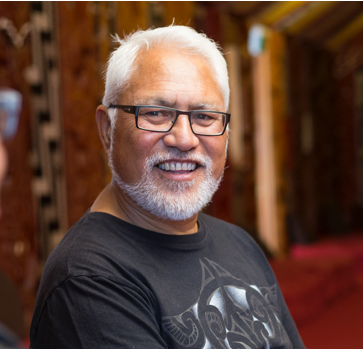 Man smiles inside a marae