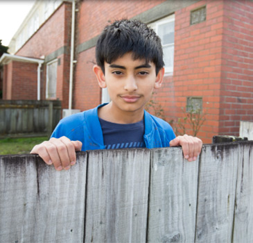 Boy looks over fence