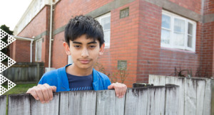 Boy looks over fence outside brick house