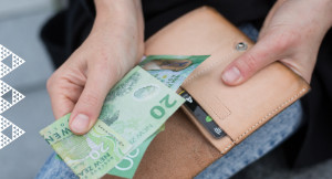 Hands holding wallet and two $20 notes